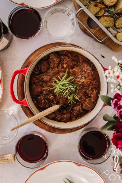 Kuvassa on punainen pata, jossa on burgundinpataa. Rosmariinia on koristeena. Kuvassa on myös punavalkoisia lautasia sekä hieman sumeita kukkia.