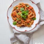 Valkoisella lautasella pasta-annos. Päällä lehtipersiljaa.