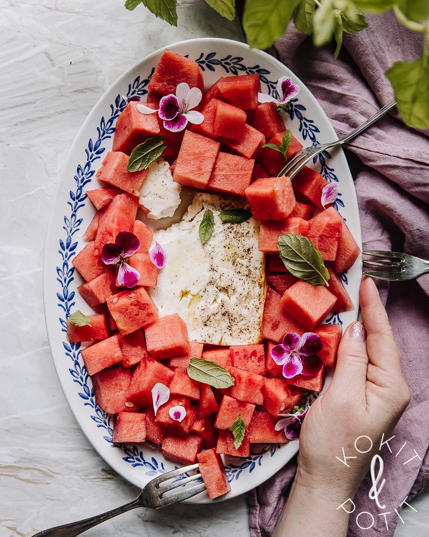 Soikealla lautasella vesimelonikuutioita ja keskellä uunifeta. Päällä minttua ja syötäviä kukkia. Käsi pitää lautasesta kiinni.