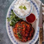 Soikealla lautasella on kulhossa riisiä sekä paahdettu kukkakaali, joka on tummanpunainen gochujang-maustetahnan vuoksi.