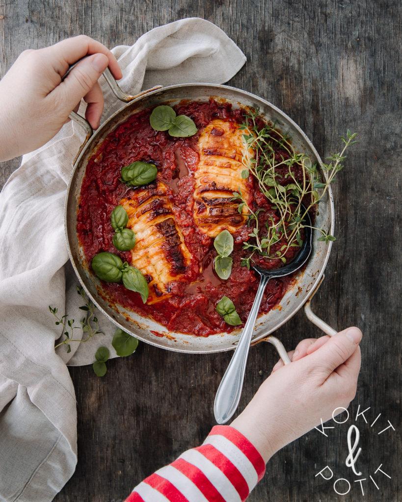 Uunivuoka, jossa on tomaattikastiketta ja paahdettua halloumijuustoa. Päällä yrttejä. Kuvassa on kädet.