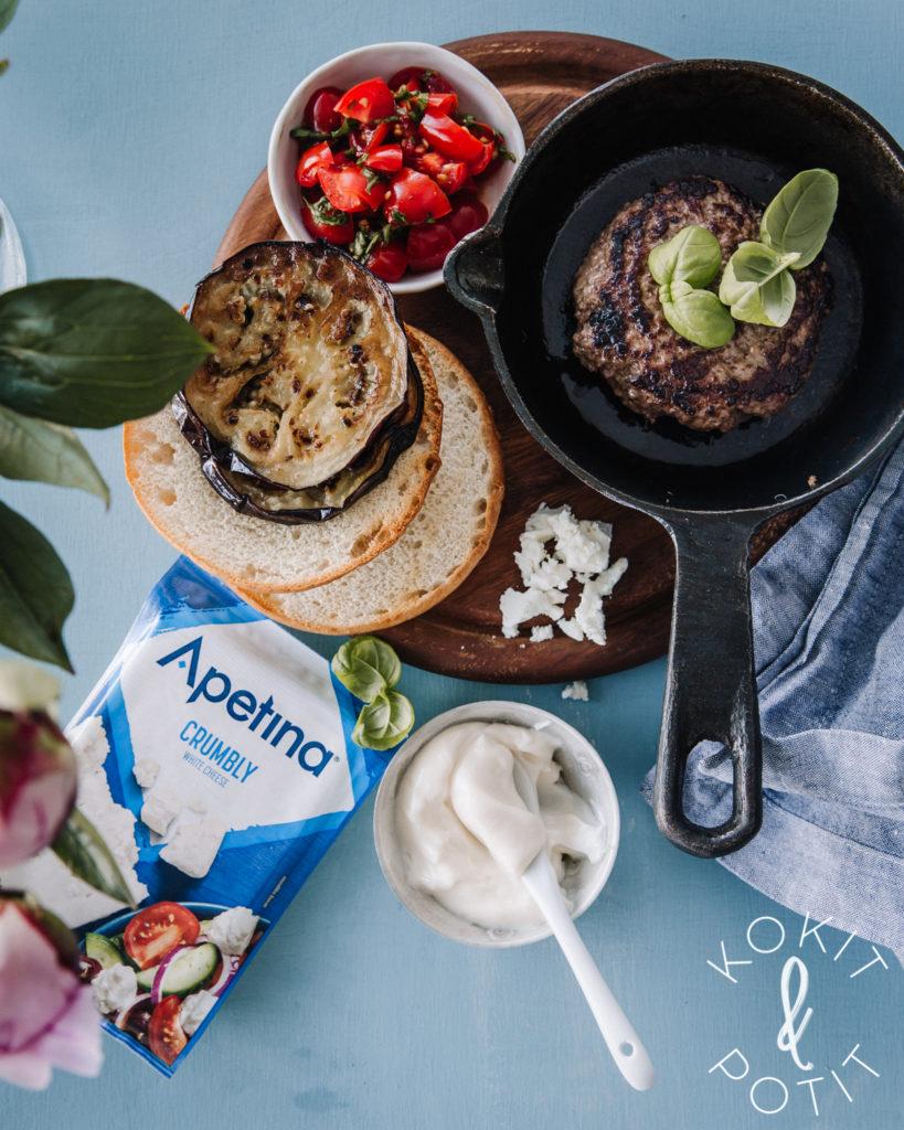 Hampurilaiset osaset: pihvi paistinpannulla, tomaattisalsa, paistetut munakoisot, murusteltu juusto, sämpylät ja yrttejä.
