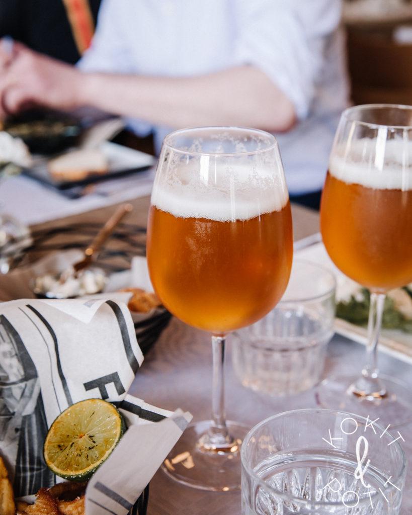 Ravintolapöydässä on kaksi huurteista olutlasia ja ruokalautasten kulmia.
