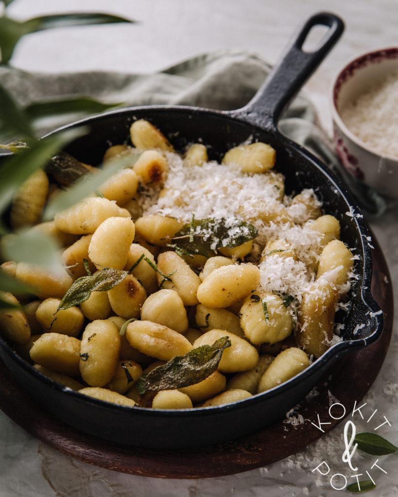 Valurautapannulla on paistettuja gnoccheja, päällä parmesaania ja rapeita salvianlehtiä.