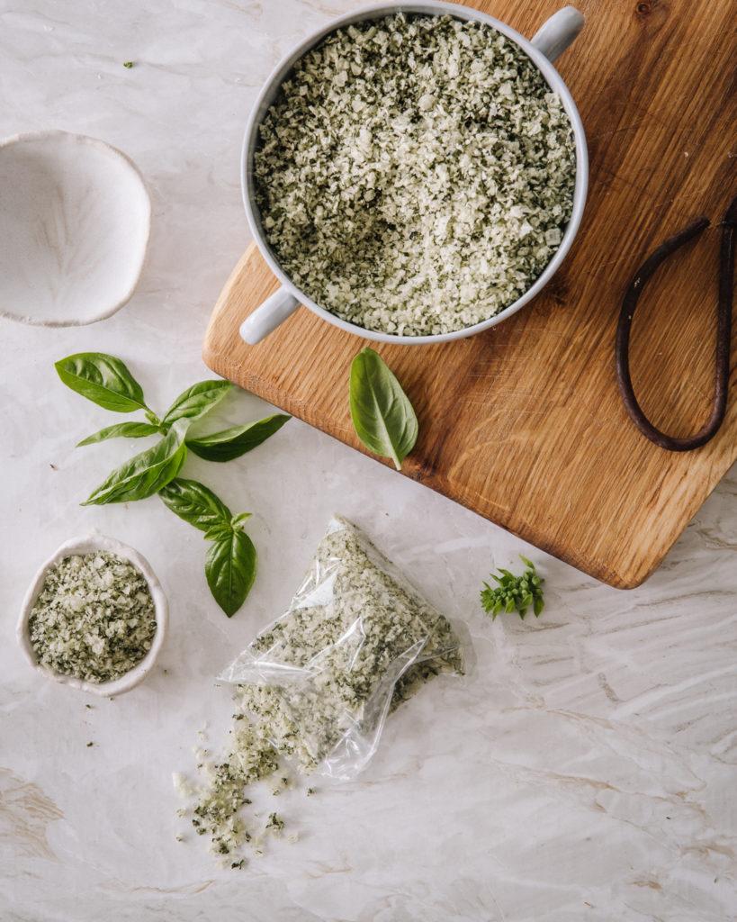 Vihreää yrttisuolaa kahvallisessa kulhossa sekä pienessä keraamisessa kulhossa ja lahjapussissa.