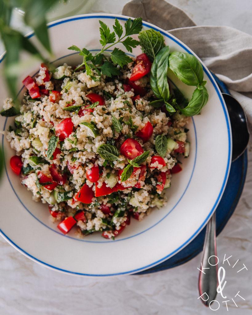 Lautasella on tabbouleh-salaattia, joka on tehty kvinoasta. Koristeena yrttejä.
