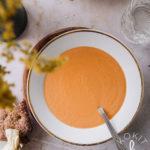 Hehkuvan oranssi keitto valkoisella lautasella.