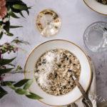 Valkoisella lautasella on sienirisottoa. Kuvassa on myös viinilasi ja vesilasi.