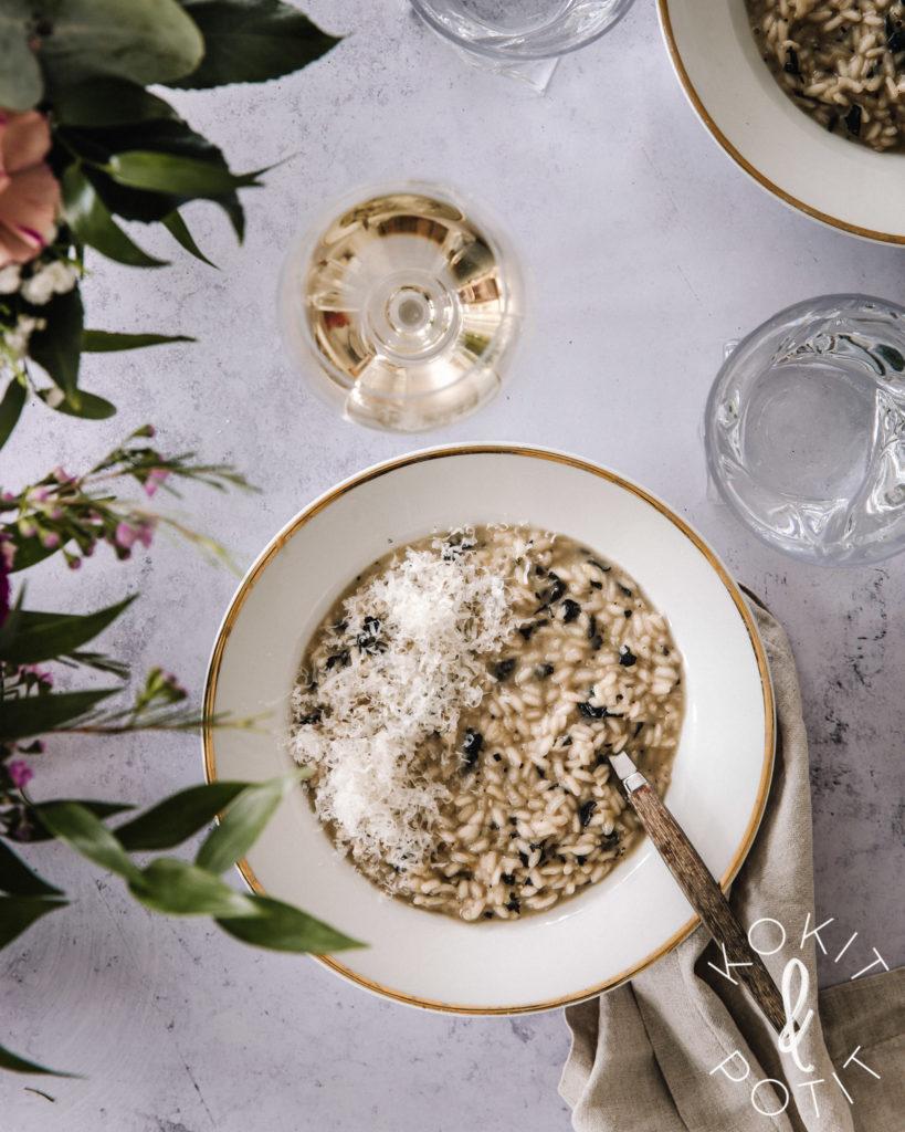 Valkoisella lautasella on sienirisottoa, jonka päällä on parmesaaniraastetta. Kuvassa on myös kaksi vesilasia ja viinilasi, jossa on valkoviiniä.