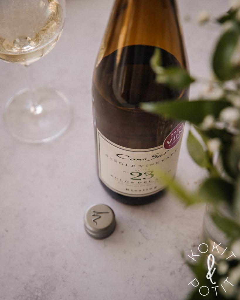 Kuvassa on valkoviinipullo, viinilasi, viinipullon kierrekorkki ja epätarkkoja vihreitä kukkien lehtiä.