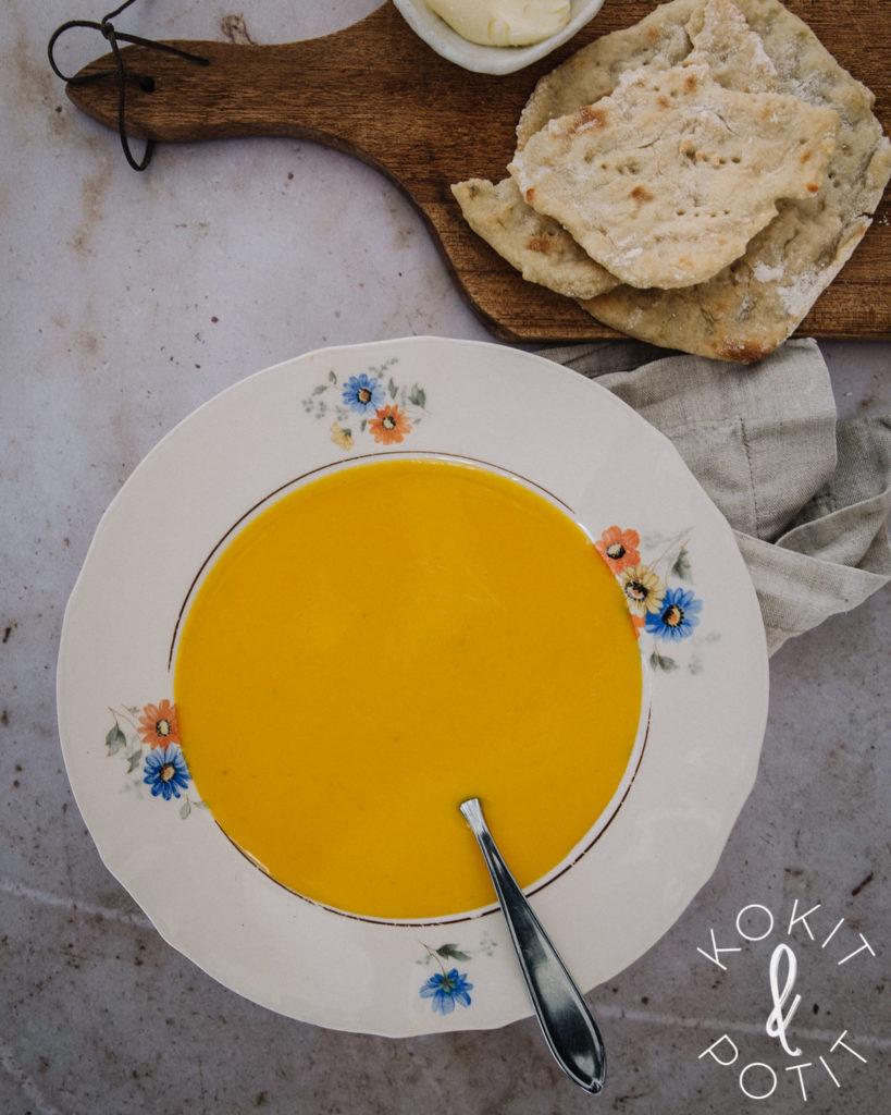 Keltaista kurpitsakeittoa kukkareunaisella lautasella. Kuvan ylälaidassa on perunarieskoja puualustalla.