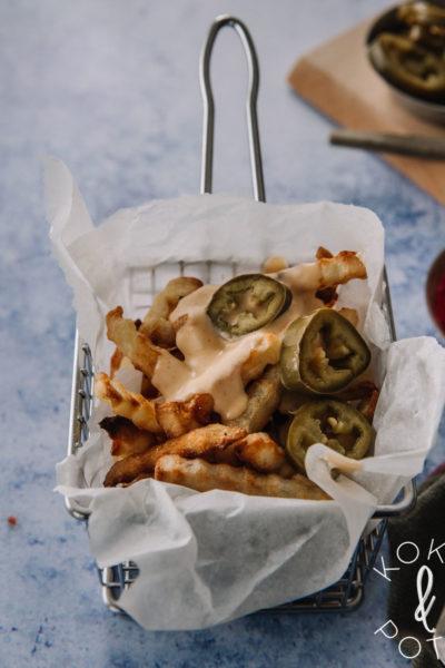 Kahvallisessa metallikorissa on leivinpaperi ja ranskalaisia. Ranskalaisten päällä on juustokastiketta ja jalapenosiivuja.