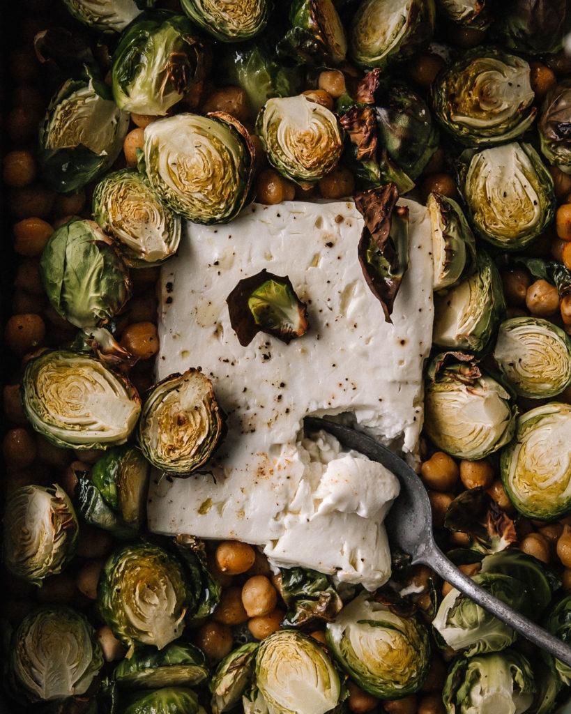 Lähikuva uunivuoasta, jossa on uunifetaa, paahtuneita ruusukaaleja sekä mausteisia kikherneitä.