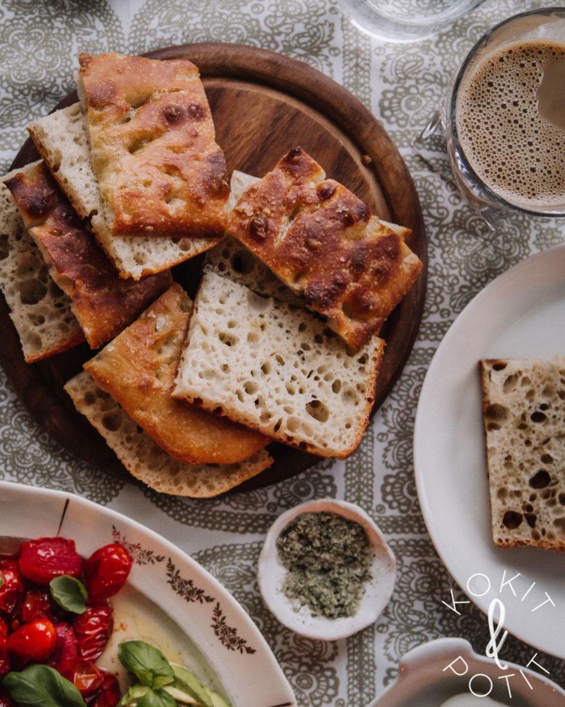 Aamupalapöydässä on hapanjuurifocacciaa halkaistuina paloina, maitokahvia ja kulma astiasta, jossa on paahdettuka tomaatteja.