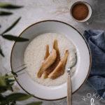 Valkoisella, kultareunaisella lautasella on helmipuuroa. Puuron päällä on voissa paistettuja päärynäviipaleita, joihin päälle on ripoteltu kanelia.