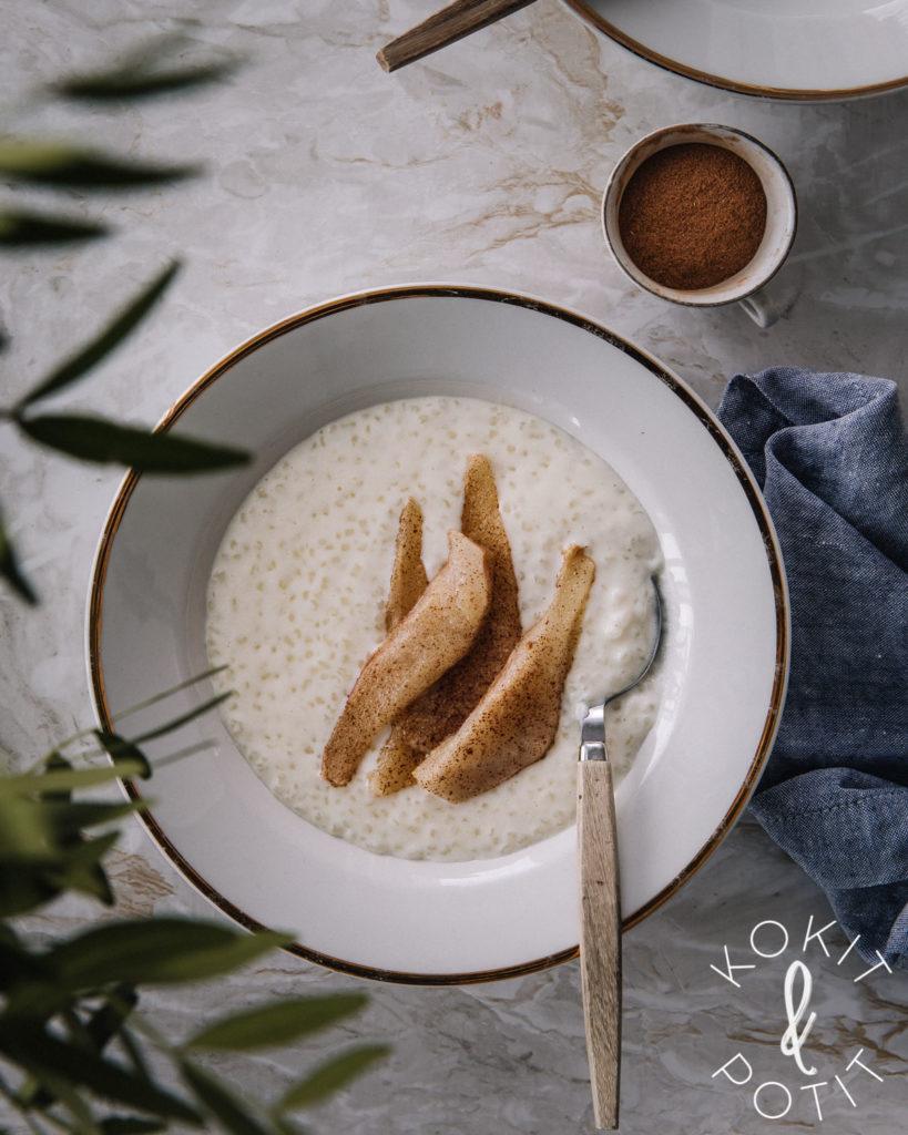 Valkoisella, kultareunaisella lautasella on helmipuuroa. päällä on kanelilla maustettuja, paistettuja päärynäviipaleita.