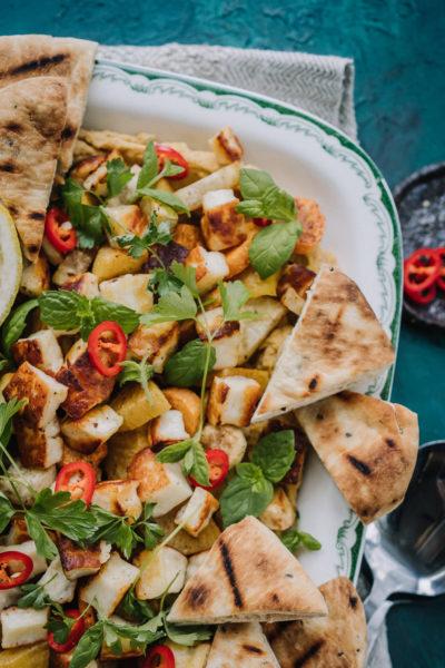 Värikäs kasvisruoka, jossa on päällä yrttejä ja sitruunaa.