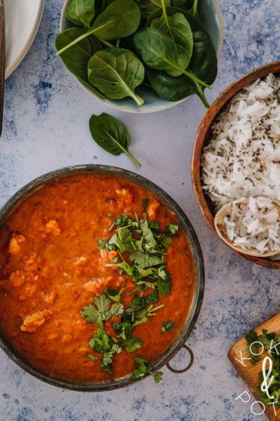 Sinisellä pöydällä on kolme kulhoa. Yhdessä on curry, toisessa riisiä ja kolmannessa tuoretta pinaattia.