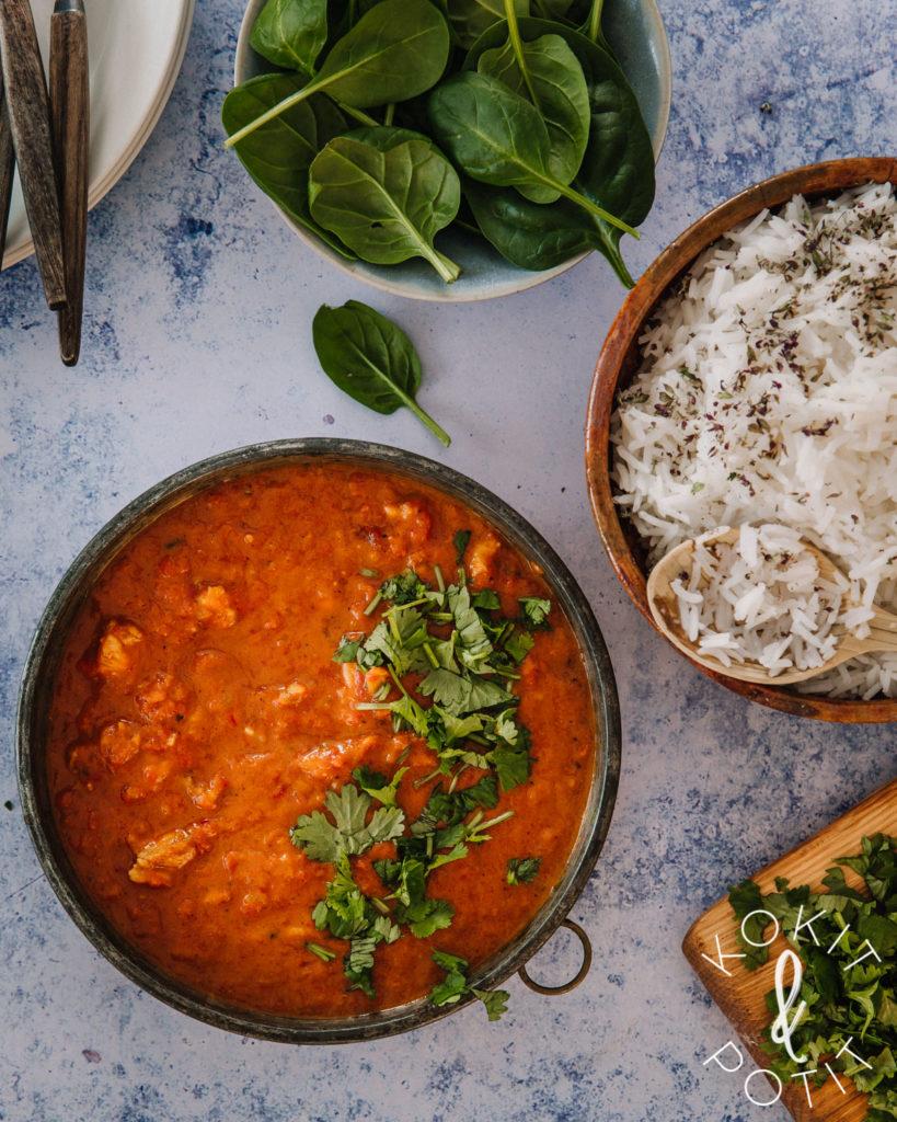 Sinisellä pöydällä onko kolme kulhoa. Yhdessä on curry, toisessa riisiä ja kolmannessa tuoretta pinaattia. Yksi pinaatinlehti on pudonnut pöydälle.