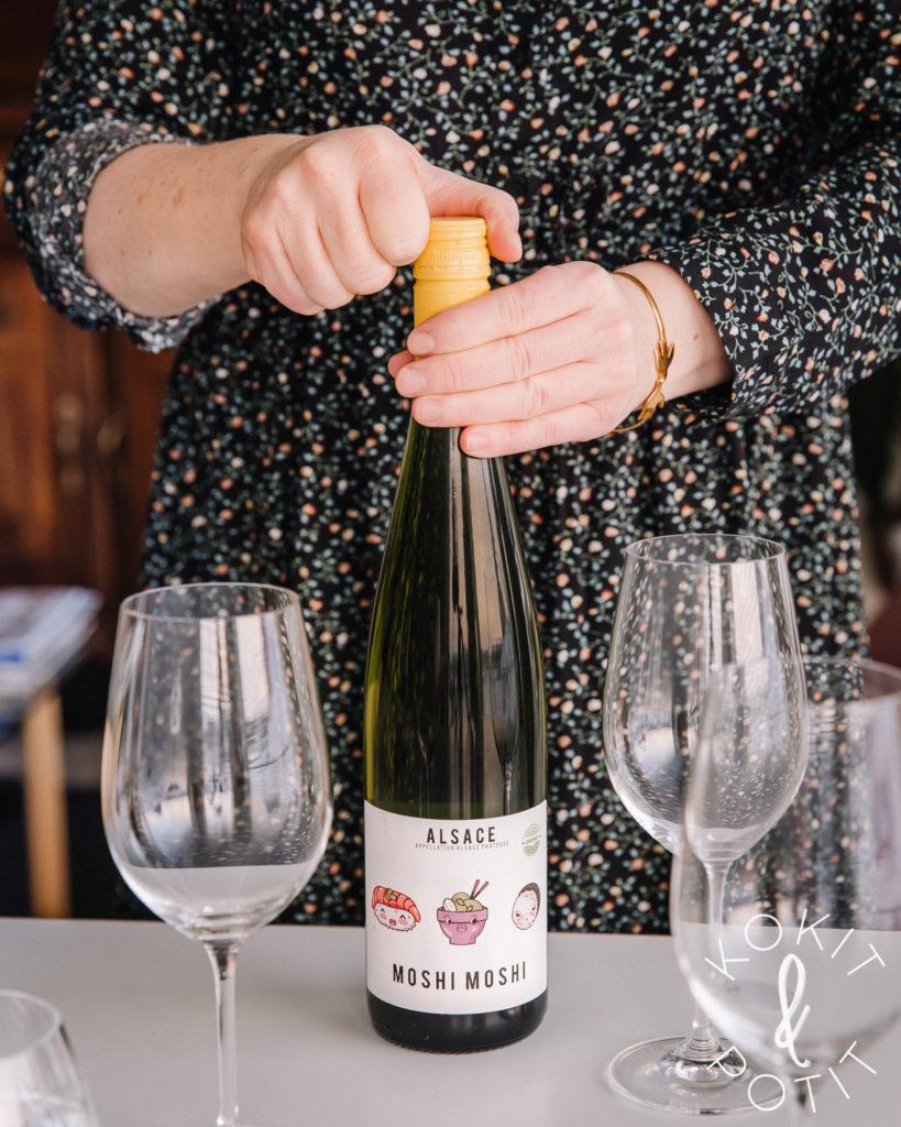 Pöydällä on viinilaseja ja viinipullo, jota nainen on juuri avaamassa.