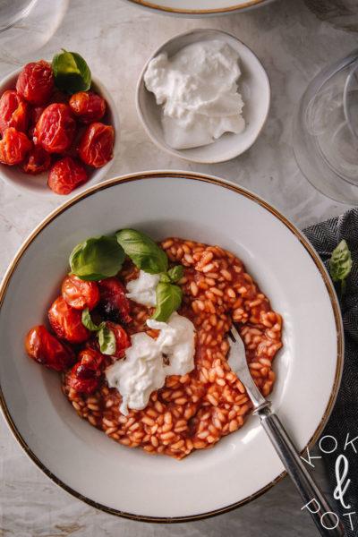 Valkoisella lautasella on tomaattirisottoa, jonka päällä on burrataa, basilikaa ja paahdettuja tomaattia. Burrataa ja tomaatteja on tarjolla myös pienillä lautasilla ison lautasen vieressä.