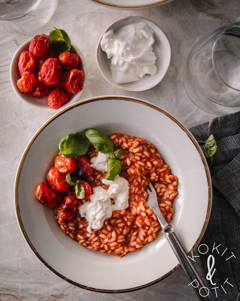 Tomaattirisotto. Kuvassa ruoka on valkoisella lautasella. Päällä on burrataa, basilikaa ja paahdettuja tomaatteja