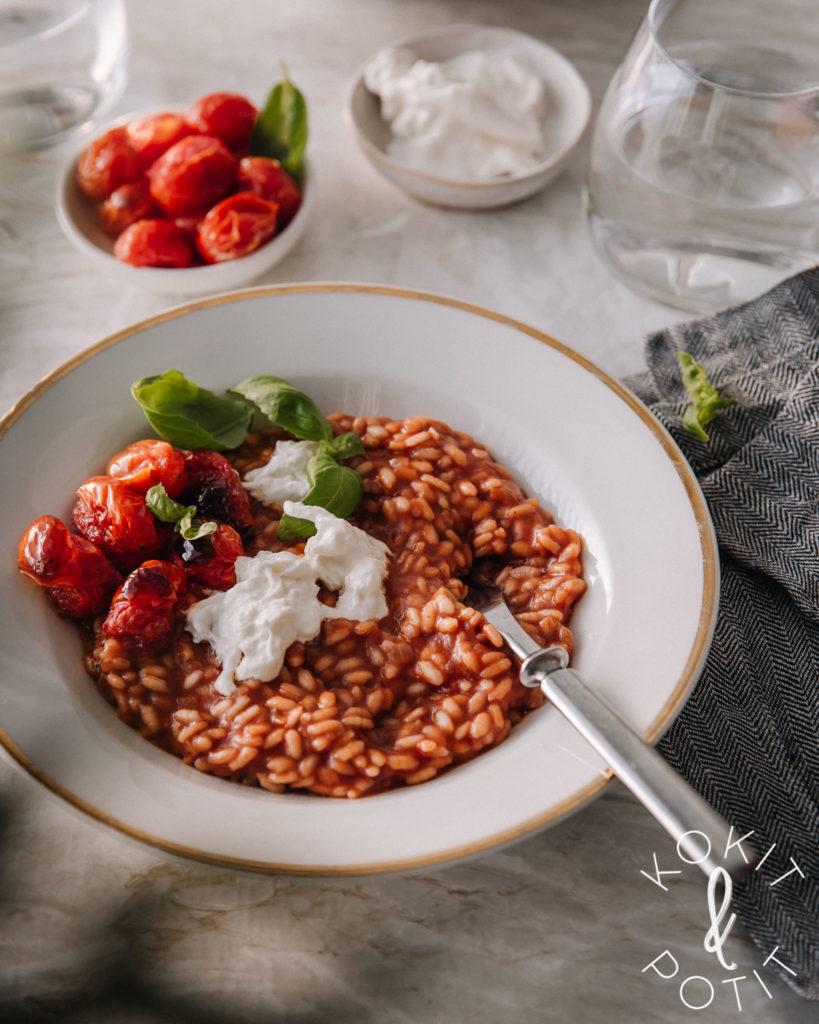 Tomaattirisotto. Kuvassa tomaattirisotto on valkoisella lautasella ja risoton päällä on burrataa, basilikaa ja paahdettuja tomaatteja.