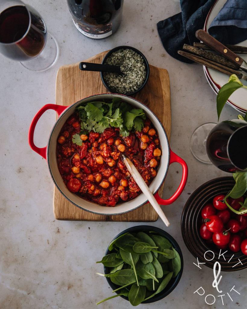 Chorizopata on pyöreässä punaisessa padassa. Lisäksi kuvassa on tuoretta pinaattia ja kirsikkatomaatteja pienissä kulhoissa.
