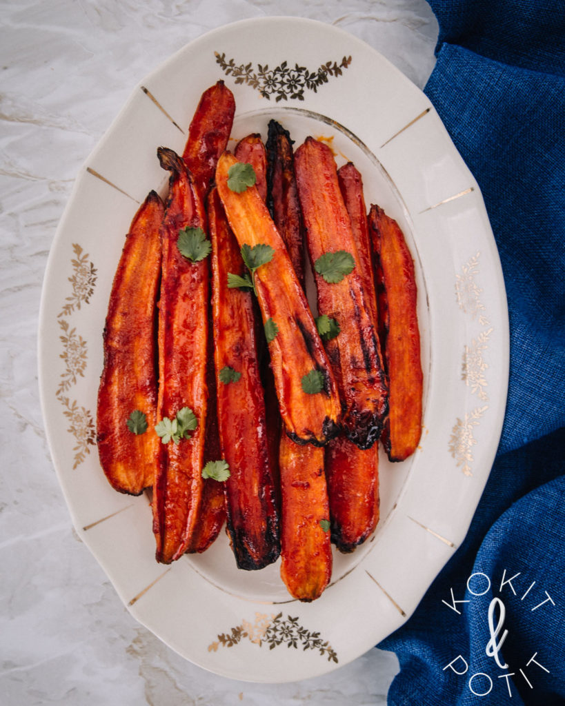 Gochujang-porkkanat ovat soikealla vadilla. Porkkanoiden päällä on muutama korianterin lehti.
