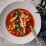 Valkoisella lautasella on tomaattinen kanakeitto, jossa on myös maissia. Keiton päällä on silputtua korianteria.