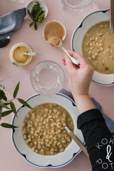 Hernekeitto. Keittoa on kahdella valkoisella, sinireunaisella lautasella. Kahdessa pienessä kipossa on sinappia. Toista sinappukulhoa kohti kurottautuu käsi, jossa on lusikka.
