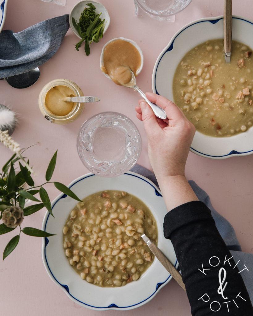 Hernekeitto on kahdella valkoisella lautasella, joissa on siniset reunat. Pöydässä on myös vesilasit ja kaksi sinappikippoa. Toiseen sinappikippoon kurottautuu käsi, jossa on pikkulusikka.