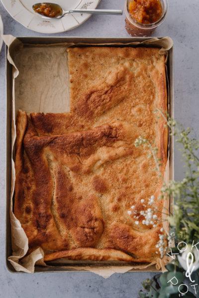 Maailman paras pannukakku on isossa uunivuoassa. Pannarista on leikattu pala pois. Kuva yläreunassa on kaksi lautasta, joista näkyy vain reunat.