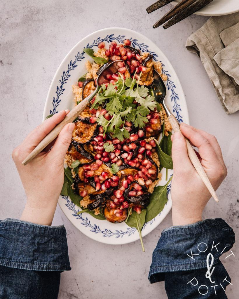 Munakoiso-kvinoasalaatti on lautasella. Kuvassa näkyy kädet, joilla otetaan salaattia puupäisillä salaatinottimilla.