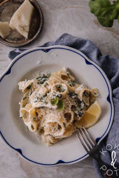 Pinaatti-ricottapasta on valkoisella lautasella, jossa on sininen reuna. Pasta on leveää nauhapastaa ja päällä on hieman pecorinoraastetta.