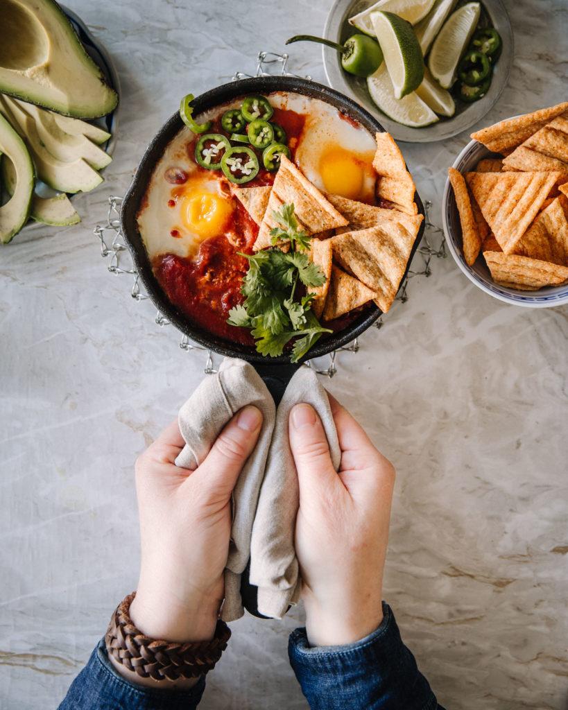 Huevos Rancheros on helppo ruoka. Kuvassa ruoka on valurautapannussa. Lisäksi kuvassa on limen lohkoja, Oikia kauranaksuja ja avokadoa. Pannua pidetään kiinni kahdella kädellä.