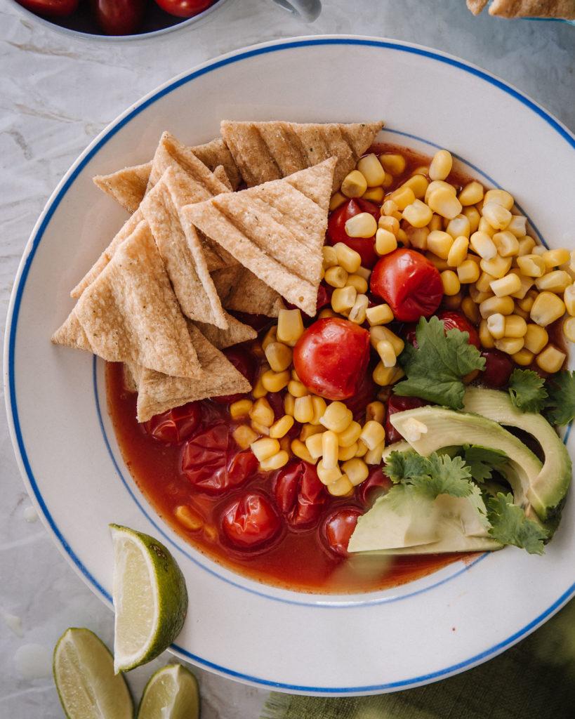 Meksikolainen tomaattikeitto on valkoisella lautasella. Päällä on avokadoa, kauranaksuja ja tuoretta korianteria. Keitossa on myös maissia.
