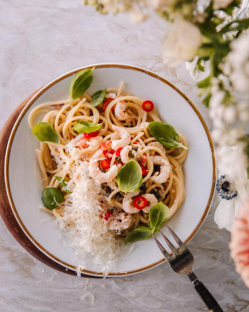 Sitruunainen katkarapupasta on valkoisella lautasella, jossa on kultainen reuna. Kuvan oikeassa reunassa on kukkia.