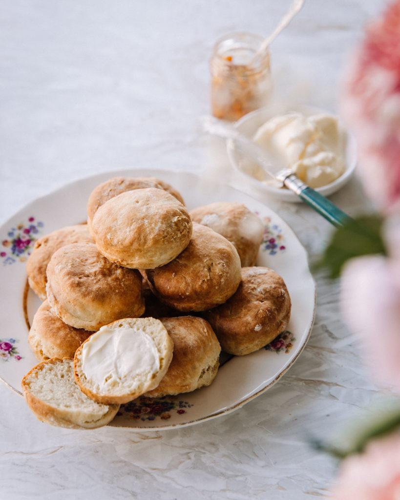 Skonssit eli helpot englantilaiset teeleivät. Kuvassa skonssit ovat kukkareunaisella lautasella kasassa.