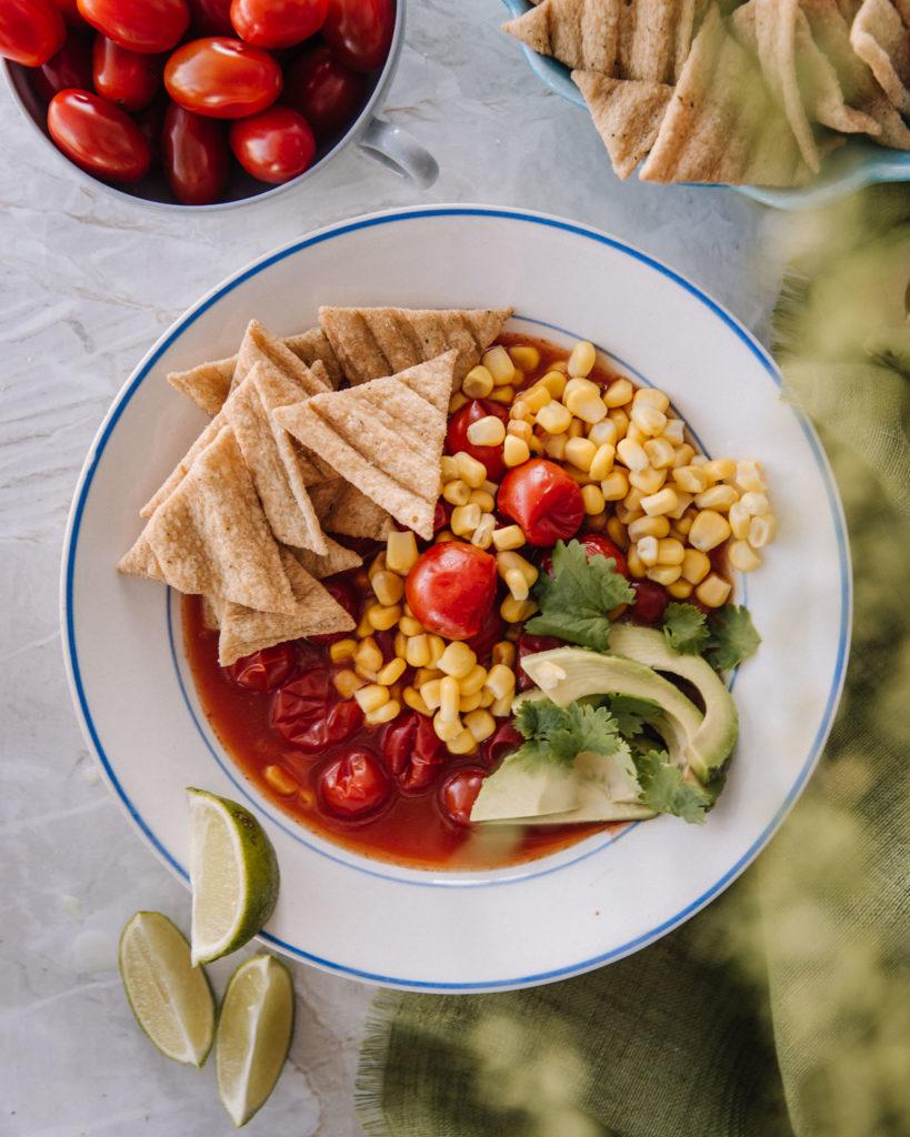 Meksikolainen tomaattikeitto on valkoisella lautasella, jossa on sininen reuna. Kuvassa on myös kolmionmallisia Oatis-kaurasnackseja sekä kirsikkatomaatteja.