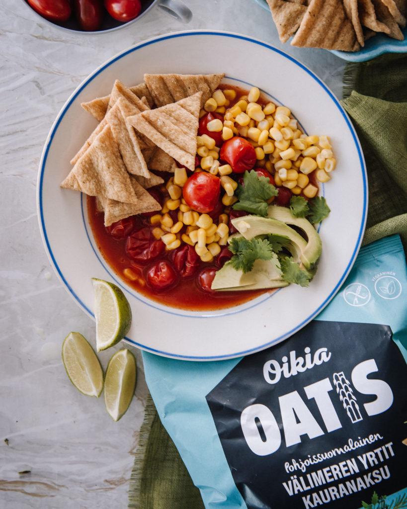 Tomaattikeitto, jonka päällä on Oatis-kaurasnackseja, avokadoa ja korianteria.
