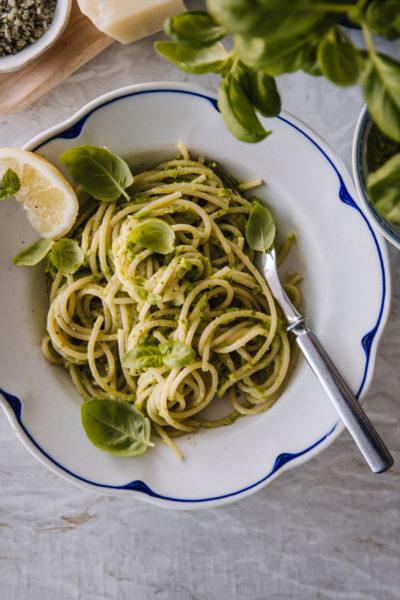 Hernepestopasta on tehty speghetista. Ruoan päällä on basilikanlehtiä ja valkoisen, sinireunuksisen lautasen reunalla on sitruunaviipale.