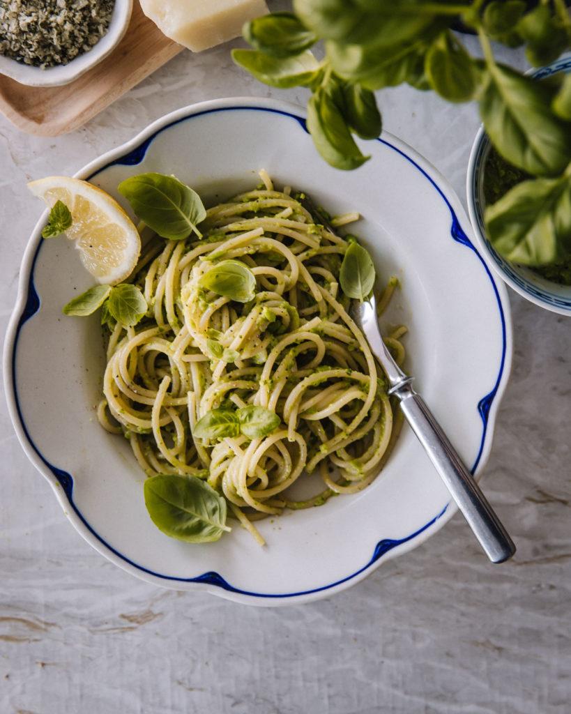 Hernepestopasta on tehty spaghettiin. Ruoan päällä on basilkanlehtiä ja lautasen reunalla sitruunaviipale.