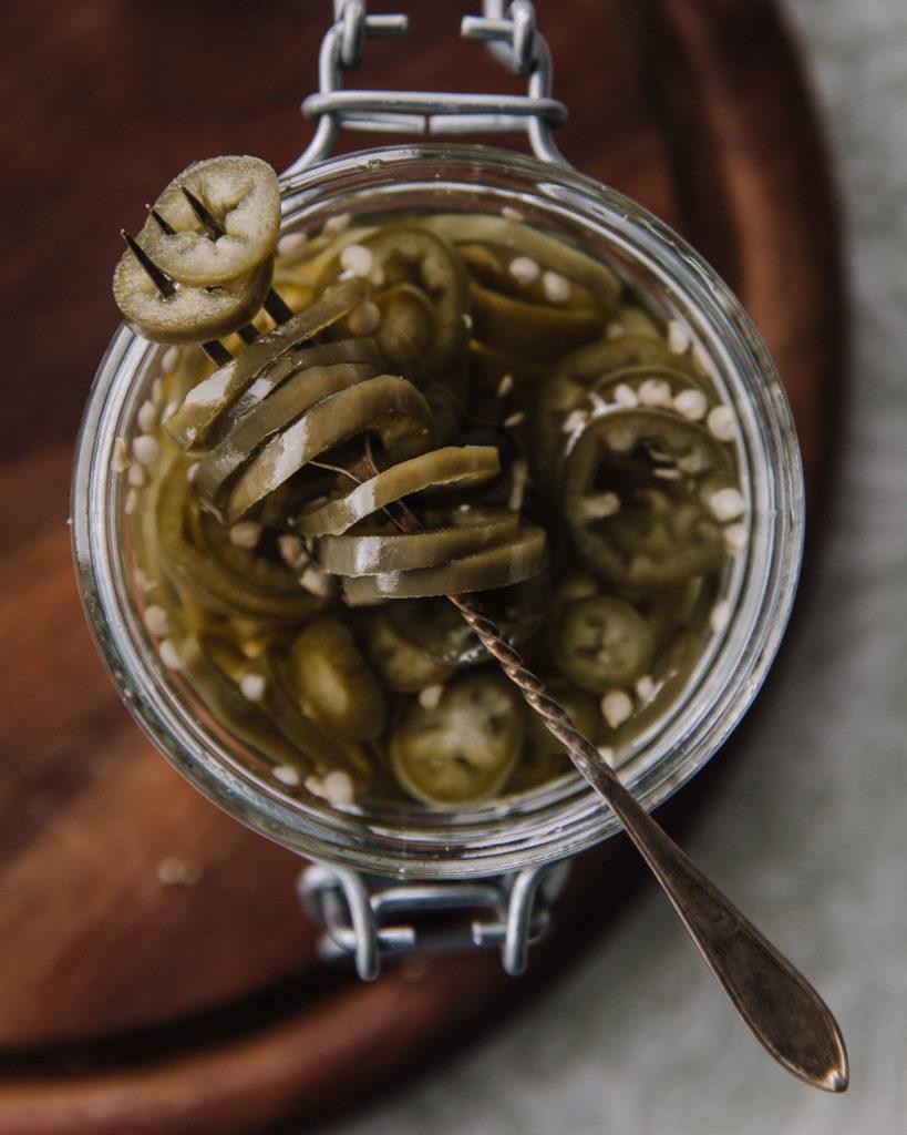 Pikkelöidyt jalapenot ovat lasipurkissa. Kuva on otettu ylhäältäpäin ja jalapenoviipaleita on pienessä haarukassa.