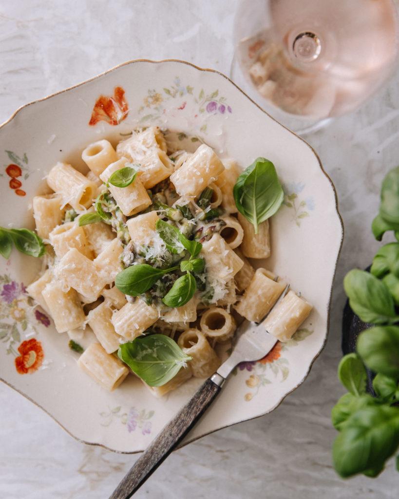 Sitruuna-parsapasta on kauniilla lautasella. Pasta päällä on tuoreita basilikanlehtiä sekä parmesaania. Pöytä on vaaleaa marmoria. Kuvassa on myös roseviinilasi sekä basilkaruukku.