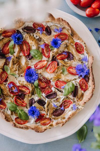 Välimeren piirakka, jossa on täytteenä artisokkaa, oliiveja ja uunissa paahtuneita tomaatteja. Koristeena on ruiskaunokkeja.