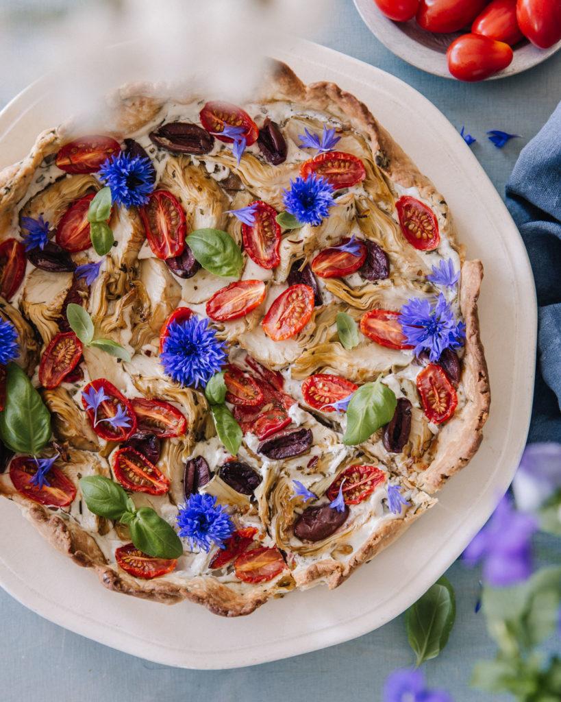 Välimeren piirakka, jossa on latva-artisokkaa, oliiveja ja kirsikkatomaatteja. Päällä on ruiskaunokkeja sekä basilikan lehtiä. Piiras on luonnonvaalealla, hieman aaltoilevareunaisella lautasella.