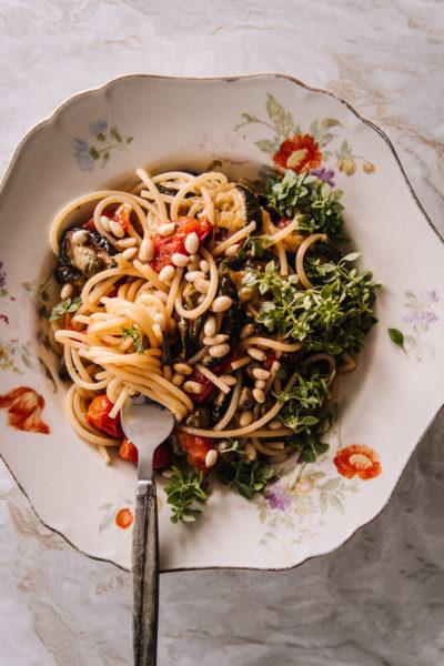 Kesäkurpitsapasta on Arabian vanhalla lautasella, jonka reuna on aaltoileva ja kukkaisa. Pastan päällä on pinjansiemeniä ja pienilehtistä basilikaa.