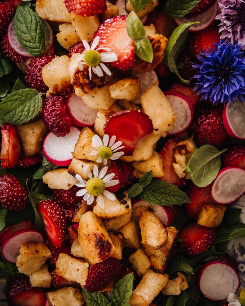Mansikka-halloumisalaatin päällä on minttua, basilikaa sekä syötäviä kukkia.