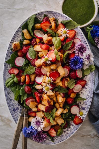 Mansikka-halloumisalaatti on sini-valkoisella, soikealla lautasella. Salaatin päällä on minttua, basilikaa sekä syötäviä kukkia. Kastike on pienessä kulhossa kuvan ylälaidassa.
